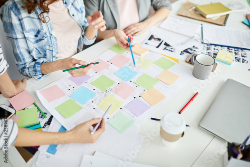 High angle closeup of creative business team planning project placing colorful stickers on roadmap, copy space
