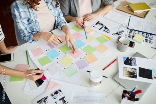 Fototapeta High angle closeup of contemporary business team planning project placing colorful stickers on roadmap, copy space obraz