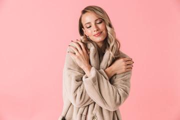 Beautiful young blonde woman wearing winter fur coat