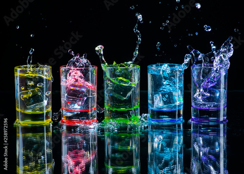 La pose en embrasure Alcool Multicolored glasses filled with alcoholic drinks, with splases of ice cubes falling inside, standing on the mirror surface. Black background. Conceptual, celebrated, commercial design