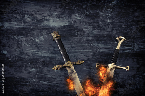 Fotografie, Tablou  low key banner of silver sword in the flames of fire