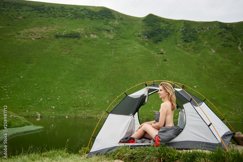 Fototapety, obrazy: Side view of attractive naked woman hiker sitting in tent in sleeping bag, beautiful view of lake in the mountains on the background. Camping lifestyle concept adventure summer vacations outdoor
