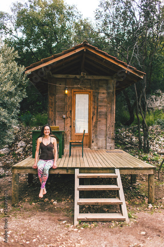 Fotografía  A woman is sitting on the porch of an old wooden house.