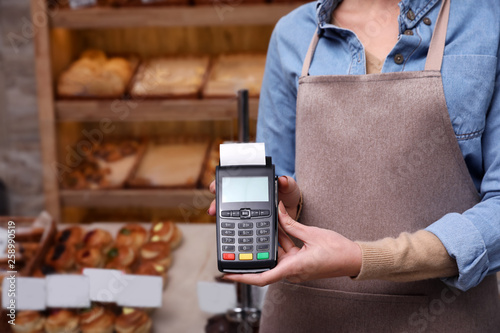 Woman holding payment terminal in bakery, closeup. Space for text Fototapet