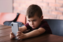 Sad Little Boy With Mobile Phone Sitting At Table Indoors