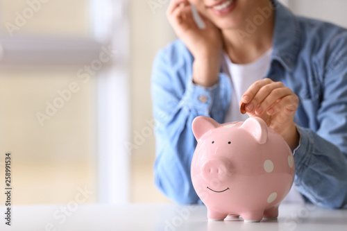 Cuadros en Lienzo Woman putting coin into piggy bank at table indoors, closeup