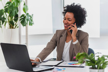 Happy Smiling African-american Business Woman Working On Laptop At Office, Using Smart Phone. Businesswoman Sitting At Her Working Place