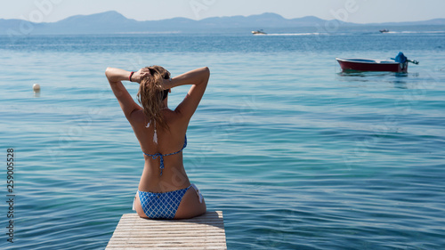 Fototapeta Beautiful Girl on The Pier. Ocean. Vacation. Mallorca island in a beautiful summer day. Beautiful beach landscape with woman on the pier. obraz