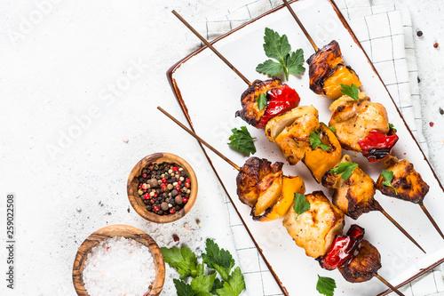 Fotomural Chicken kebab on skewers on white.