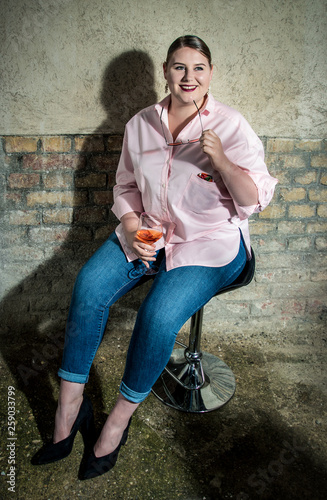 Photo  beautiful seductive girl plus size with glass prosecco, taking off her glasses