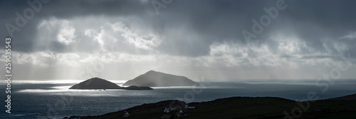 Foto auf Gartenposter Dunkelgrau a view of the wild atlantic way off the coast of the ring of kerry in ireland showing skellig michael and surrounding islands in beautiful strong light with cloudy skies
