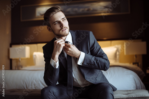 Foto Young handsome man relaxing at his apartment in a hotel after business meeting