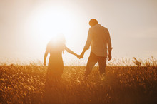 Silhouettes Of A Couple Holding Hands Looking At The Bright Sunset In A Wheat Field.