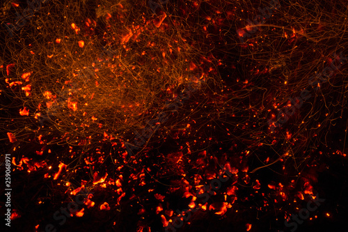 Fotografiet  Bright sparkling coals with fire as background