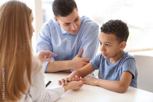 Fotografiet  Pediatrician examining African-American boy in clinic