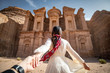 Leinwanddruck Bild - Asian woman tourist in white dress holding her couple hand at Ad Deir or El Deir, the monument carved out of rock in the ancient city of Petra, Jordan. Travel UNESCO World Heritage Site in Middle East