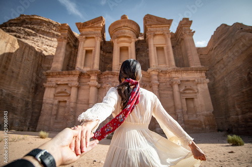 Fotografie, Obraz Asian woman tourist in white dress holding her couple hand at Ad Deir or El Deir, the monument carved out of rock in the ancient city of Petra, Jordan