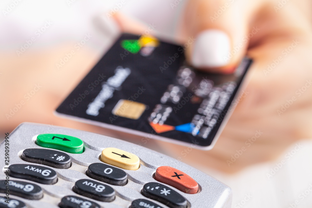 Fototapeta Paying with credit card. Female inserting chip card into payment terminal device