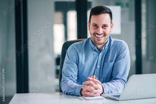 Portrait of a smiling entrepreneur or businessman at office desk.