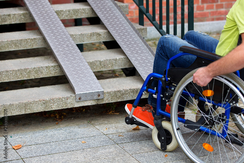 Fotografie, Obraz  man on wheelchair trying to go up the stairs
