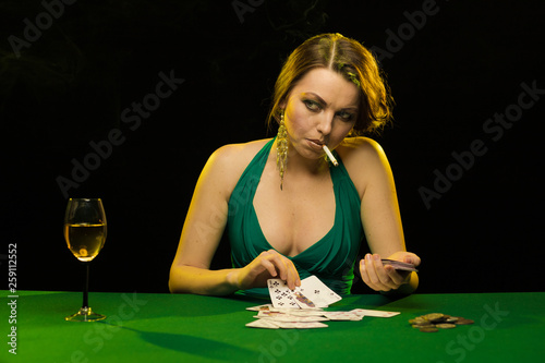 Photo  A young lady in a green dress smokes a cigarette and blows smoke and plays cards