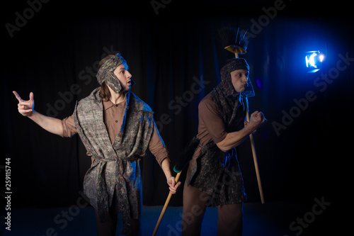 Men Actors on the stage play performance cleaners with brushes on a black backgr Fototapeta