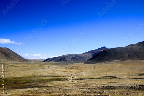 Fotobehang Donkerblauw wide panoramic view of a dry barren desert land with roads mountains and blue sky