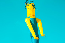 Huge Figure Of Inflatable Turquoise And Yellow Tube Man Skydancer Moving In The Air On Blue Sky Background. Kids Festival Party Celebration In City Park. Authentic Lifestyle Image Copy Space