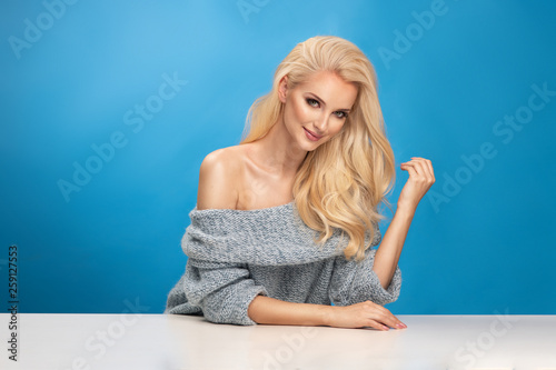 Beauty fashion portrait of blonde woman on blue background.