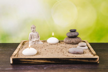 Miniature Desk Zen Sandbox With Buddha Figure Sit In Lotus Position, Stacked Zen Sea Stones, Spa Candles Burning Against Green Bokeh Studio Background, Copy Space.