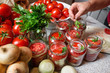 Canning fresh tomatoes with onions in jelly marinade. Woman hands putting red ripe tomato slices and onion rings in jars. Basil, parsley leaves on top of onions. Vegetable salads for winter
