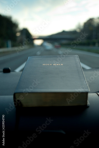 Holy Bible inside the car. Blurred auto highway background to sunset with blue sky and white clouds. Close-up. Vertical shot.
