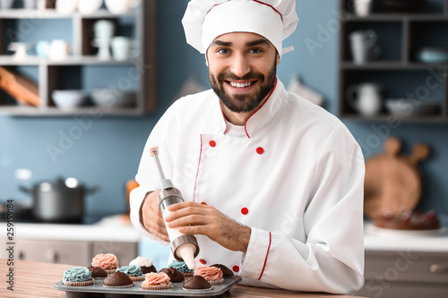 Fototapeta Male confectioner decorating tasty cupcakes in kitchen