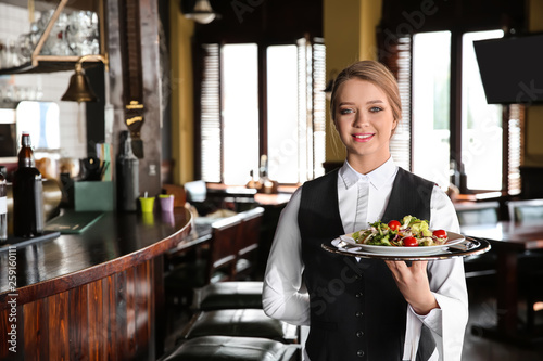 Foto auf Leinwand Akt Young female waiter with salad in restaurant