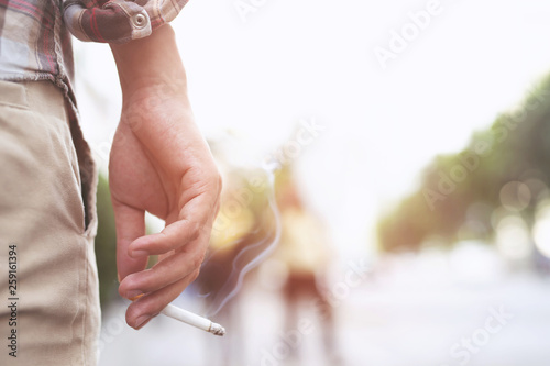 Photo man holding smoking a cigarette in hand