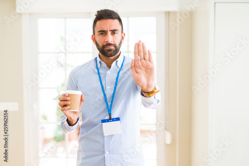 Handsome hispanic man wearing id card and drinking a cup of coffee with open han Fototapet