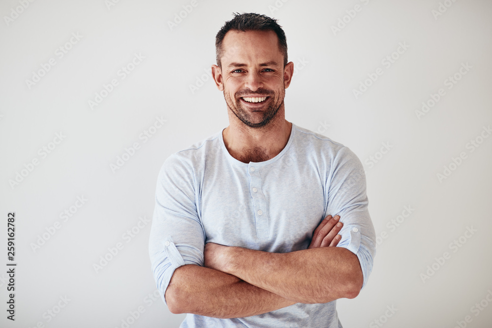 Fototapeta Mature entrepreneur standing with arms crossed on a white backgr