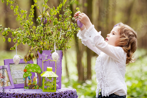 Cute little girl decorating branches with Easter eggs Wallpaper Mural