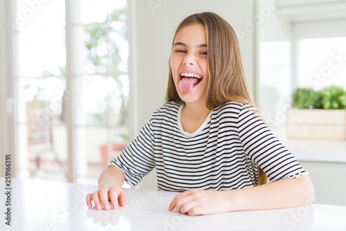 Cuadros en Lienzo Beautiful young girl kid wearing stripes t-shirt sticking tongue out happy with funny expression