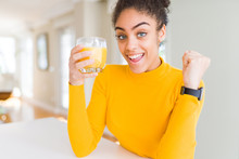 Young African American Woman Drinking A Glass Of Fresh Orange Juice Screaming Proud And Celebrating Victory And Success Very Excited, Cheering Emotion