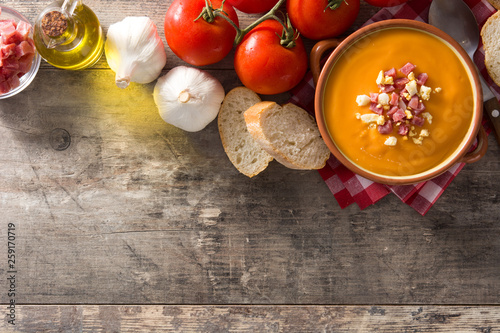 Foto  Typical Spanish salmorejo cream with ham and egg on wooden table