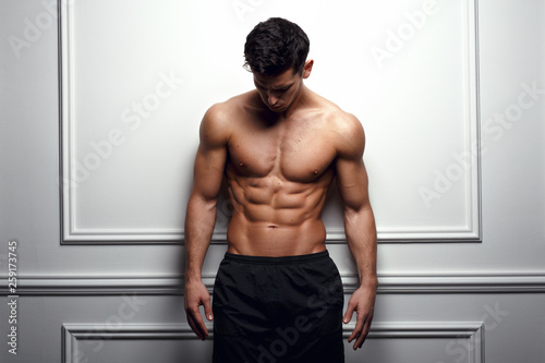 Photo  Athlete, muscular man at the white wall poses shirtless, showing six pack abs, white background