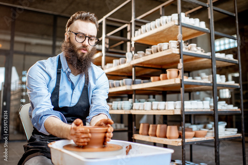 Obraz na plátne Handsome man as a potter worker in apron making clay jugs on the pottery wheel a