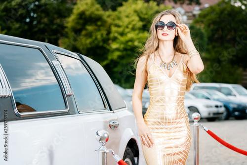 Fototapeta Woman getting out of limousine car