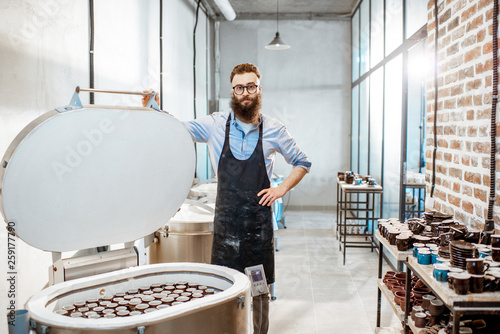 Fotografija Handsome man as a worker or business owner standing near electric ovens for cera