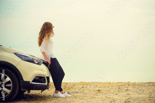 Fotomural  Happy stylish young woman traveler on beach road sitting on white crossover car, holding hat in hand