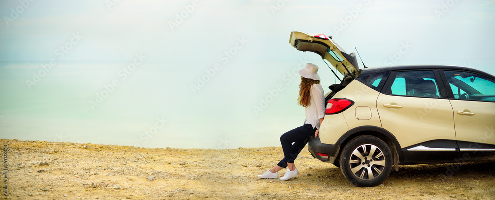 Fototapeta View of young woman traveler looking at sea sunset, sitting on hatchback car with the copy space. Banner