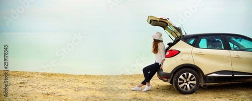 View of young woman traveler looking at sea sunset, sitting on hatchback car with the copy space. Banner