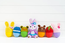 Cute Plush Bunny Doll With Colorful Easter Eggs With Crochet Easter Egg Cups Top In Various Shapes Of Bunnies, Frog, Teddy Bear, Strawberry And Pom Pom Winter Hat On White Wooden Board.
