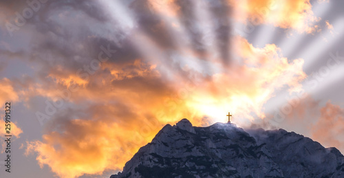 Платно Silhouette of a cross on the top of a mountain with sun rays and dramatic clouds in the background